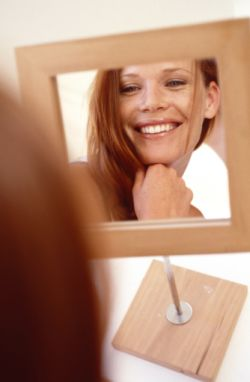 Smiling woman in mirror learned h