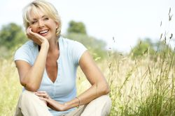 Smiling woman sitting in grass being present