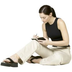 Woman sitting writing in her gratitude journal