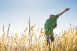 woman raising arms in nature represents positive psychology activities