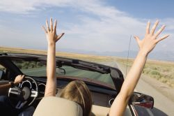 woman raising hands in convertible knows how to be happy in the moment